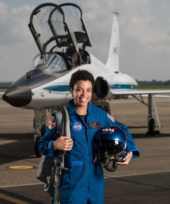 na zdjęciu jest kobieta w kostiumie astronauty, trzyma w ręku kask a za nia jest mały samolot