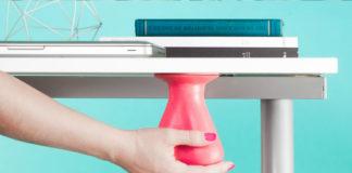 Fotografia kolorowa. Tło w kolorze jasnoniebieskim. Na zdjęciu widać fragment biurka, na którym leży zamknięty laptop i trzy kciązki czarna, biała i znów czarna. Pod blatem wisi gadżet kształten przypominający mosznę, w kolorze czerwonym. Damska dłoń trzyma gadżet od dołu.