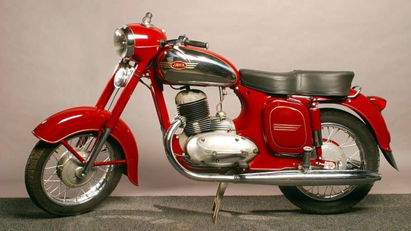 Na zdjęciu widoczny jest dawny motocykl Jawa. Stoi na jasnym tle. Jest koloru czerwonego