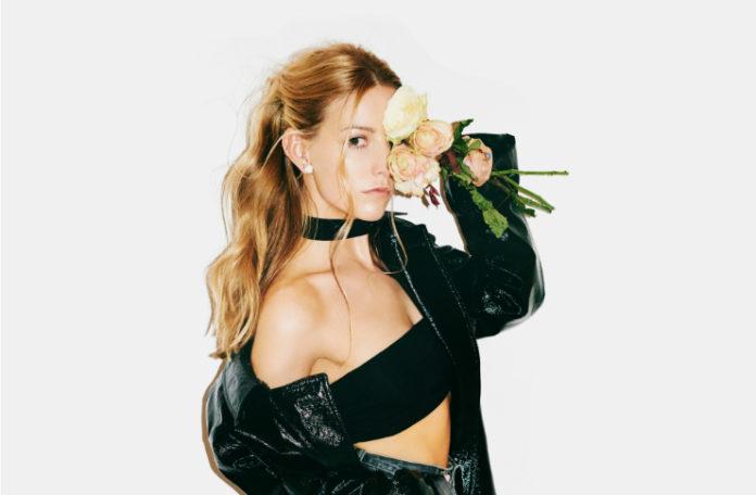Dziewczyna ubrana w czarny biustonosz, czarną kurtkę i czarny chocker trzyma kwiatek na wysokości oka