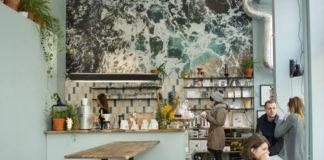 Zdjęcie przedstawia kawiarnię w środku, ladę, baristkę oraz osoby siedzące w kawiarni