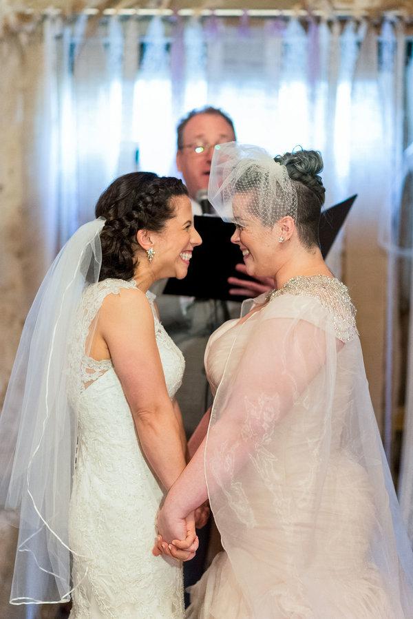 Dwie panny młode stoją przy ołtarzu, patrzą sobie w oczy, trzymają się kurczowo za ręcę i uśmiechają się szeroko do siebie wzajemnie wyraźnie zafascynowane faktem, że zostają żoną i żoną.
