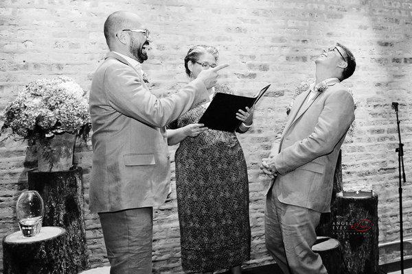 Czarnobiałą fotografia dwoch mezczyzn bioracych własnie ślub. Nie widać po nich uczucia stresu, są wyraźnie w doskonałych humorach. Obydwaj są roześmiani jakby dopiero co któryś skonczył opowiadać dowcip.