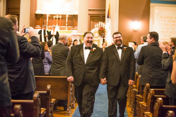 Dwóch mężczyzn idących pomiędzy ławkami wypełnionymi ludźmi