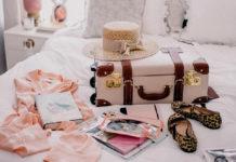 na zdjęciu jest walizka która leży na łóżku, obok walizki są poskładane ubrania oraz buty i kapelusz
