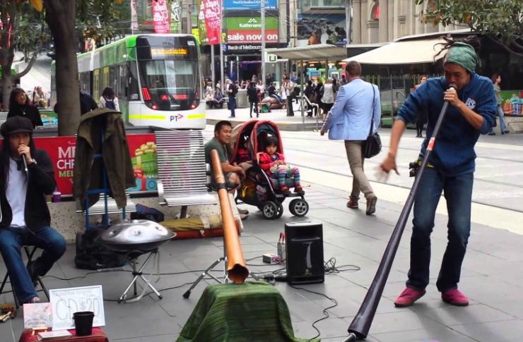 Zdjęcie muzyków ulicznych. Jeden z nich siedzi, drugi tańczy. Jeden trzyma przy ustach mikrofon, drugi gra na ukulele podłączonych do wzmacniacza. Wokół widać dużo przechodniów i jadący autobus miejski.