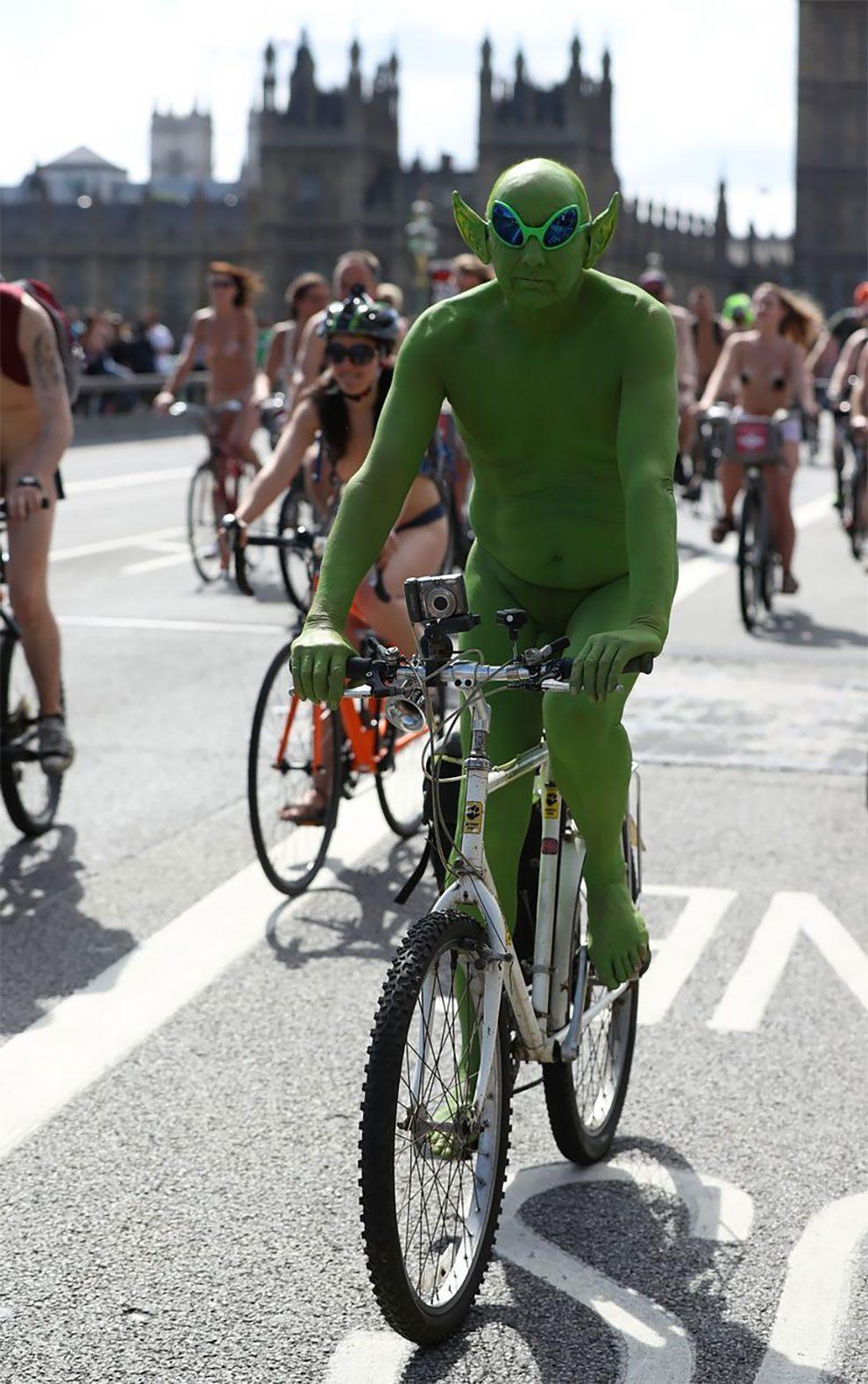 Zdjęcie uczestnika imprezy World Naked Bike Ride. Rowerzysta jest nagi i cały pomalowany zieloną farbą. Za nim widać resztę rozneglizowanych cyklistów.