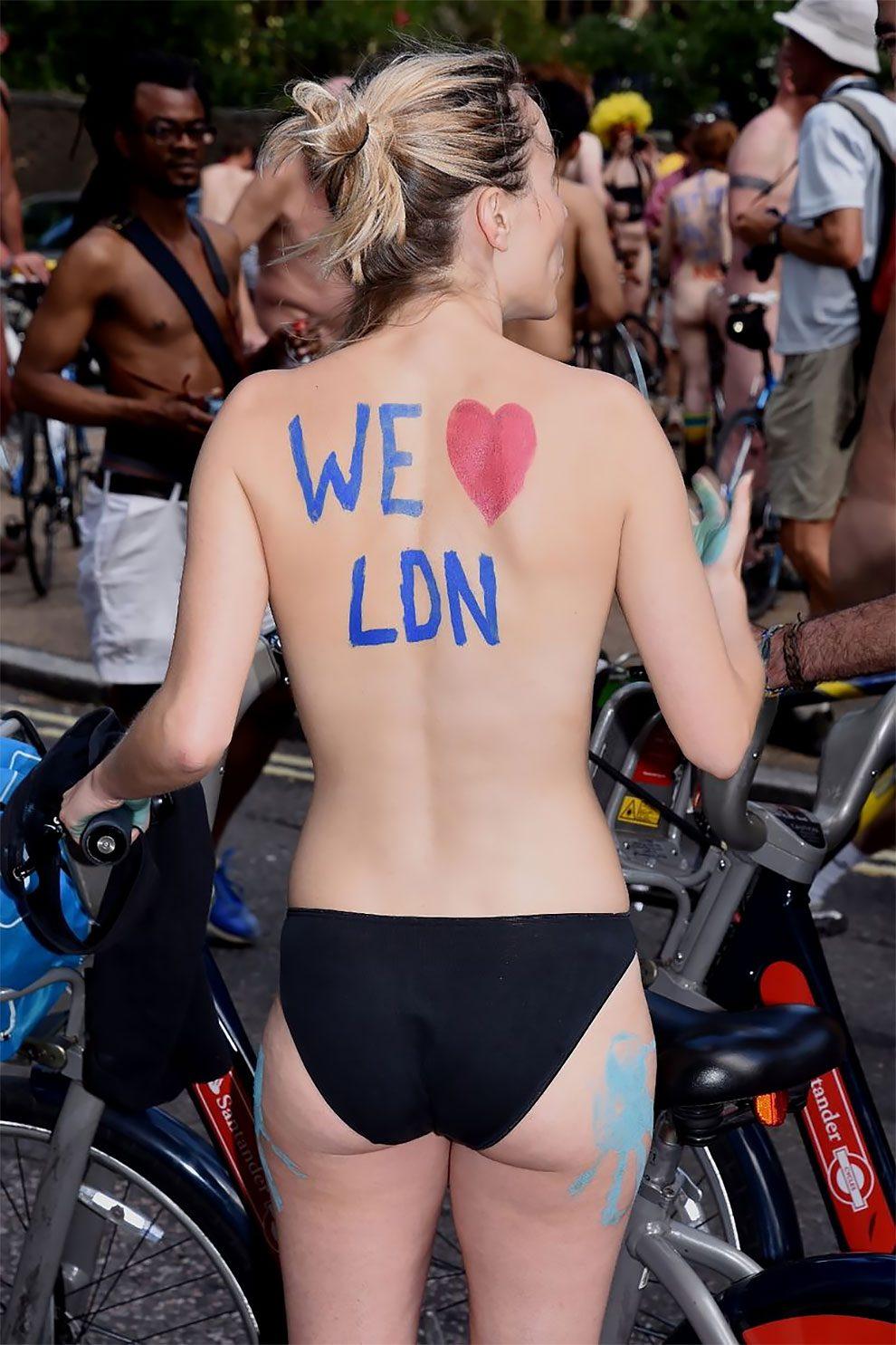 Zdjecie pleców uczestniczki World Naked Bike Ride. Kobieta stoi do fotografa tyłem, jest w samych majtkah i na jej plecach jest namalowany farbą napis i love london