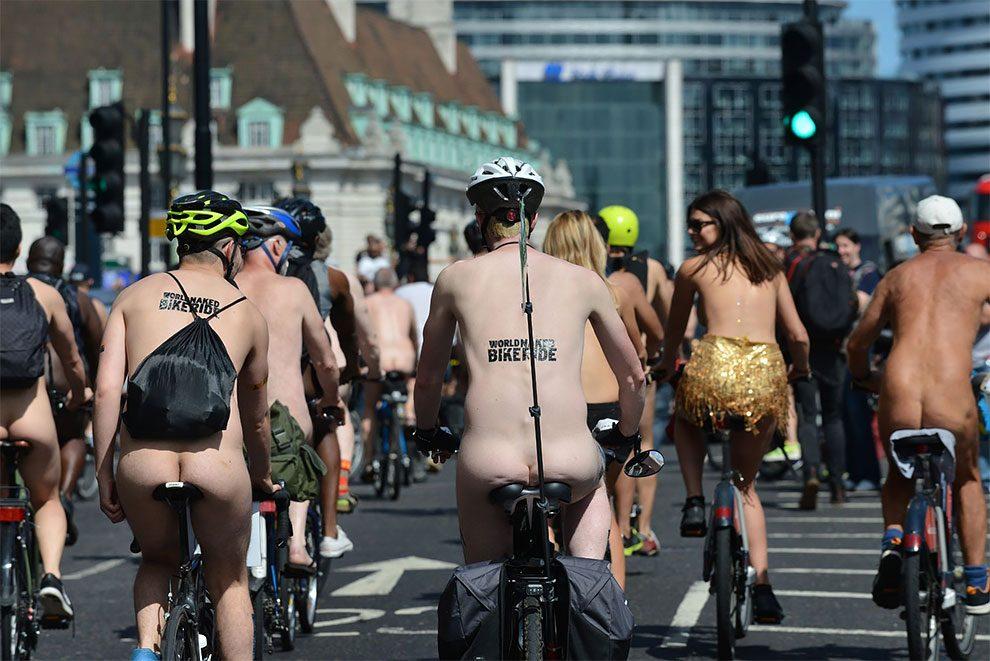 Fotografia uczestników imprezy World Naked Bike Ride. Rowerzyści, którzy są rozebrani jadą ulicami londynu. Na ich plecach widać namalowany napis głoszący nazwę imprezy.