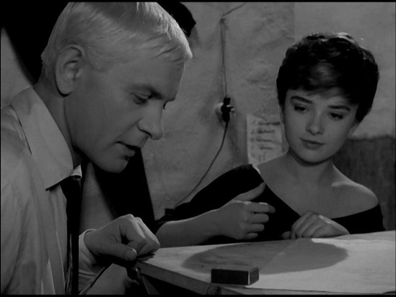 """Kadr z filmu """" Niewinni Czarodzieje"""". Przedstawia dwójke bohaterów, mezczyzne i kobiete, ktorzy siedza przy stole i bawią się paczką zapałek."""