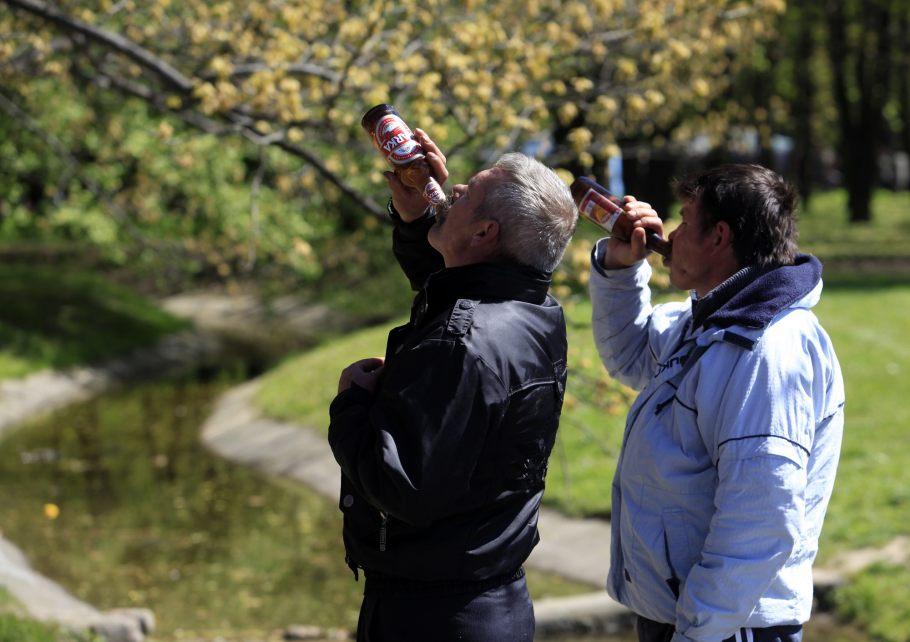 Zdjecie dwoch mezczyzn w parku ktorzy pija piwo. Jeden z nich ubrany w czarna kurtke, drugi w białą. Stoją na moście, pod nimi płynie jakiś strumuyk.