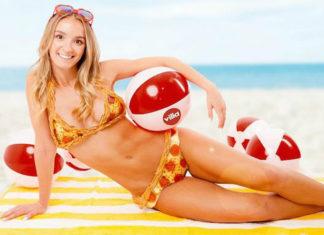 Dziewczyna ubrana w bikini z pizzy leżaca na żółto-białym ręczniku plażowym