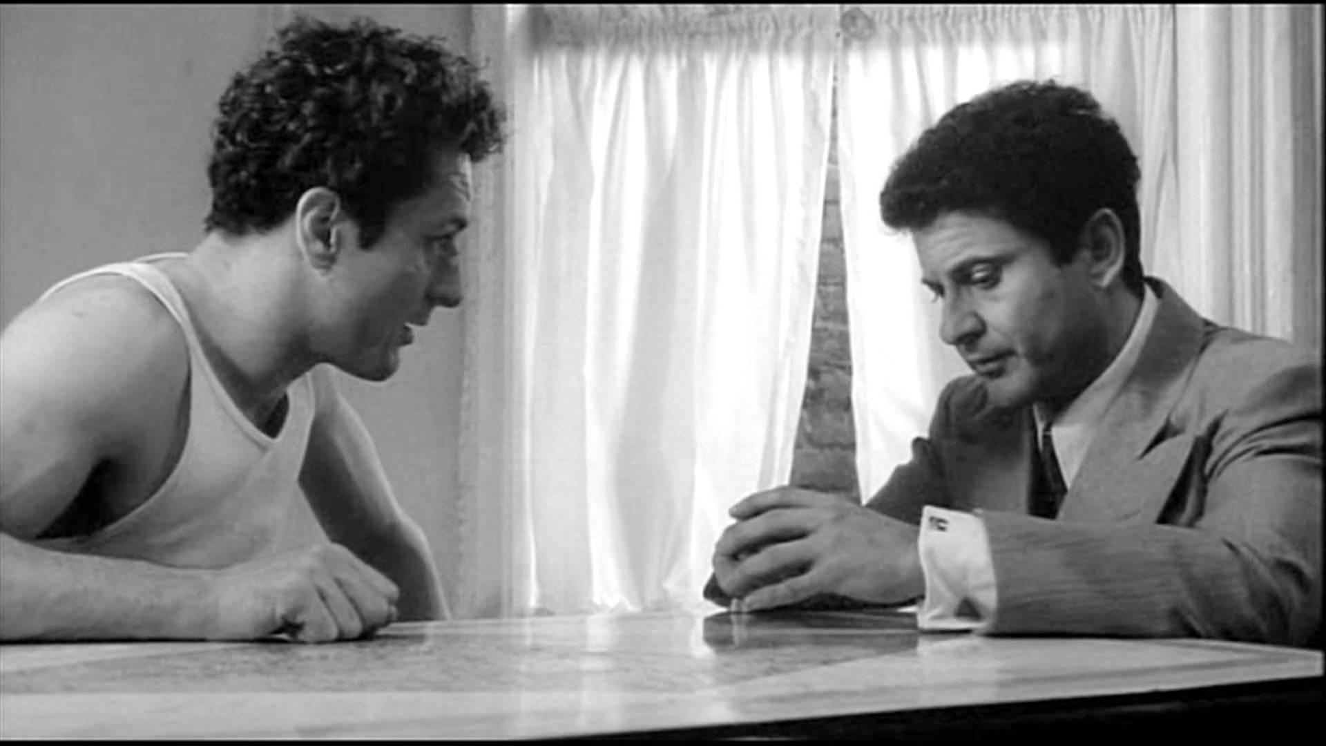 """Kadr z filmu """" Wściekły Byk"""". Widać Roberta de Niro, który prosi swojego brata, w tę role wcielił się Joe Pesi, by ten uderzył go w twaz. Robert De Niro siedzi w koszulce na ramiączka, a Joe Pesci w marynarce, koszuli i w krawacie trzyma ręce na stole sluchajac uwaznie brata."""