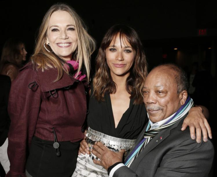 Zdjęcie trzech osob. Widoczne sa dwie kobiety oraz mezczyzna. Jedna z nich jest biała, druga jest mulatką, a mezczyzna jest czarnego koloru skóry. Blondynka to żona męzczyzny i zarazem matka jego stojącej po środku córki. Jest to zdjecie przedsawiajace Quincy Jonesa wraz z córką i jej matką. Męzczyzna siedzi, kobiety stoją.