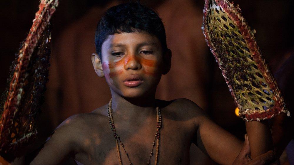Fotografia młodego chłopca z plemienia Satere Mawe, który przechodzi proces stawania się mężczyzną. W tym celu przez 10 minut ma na rękach specjalnie tkane rękawice, które wcześniej wypełnioną mrowkami buna. Stoi spokojnie z rękami podniesionymi do góry, na twarzy ma wymalowane specjalne wzory.