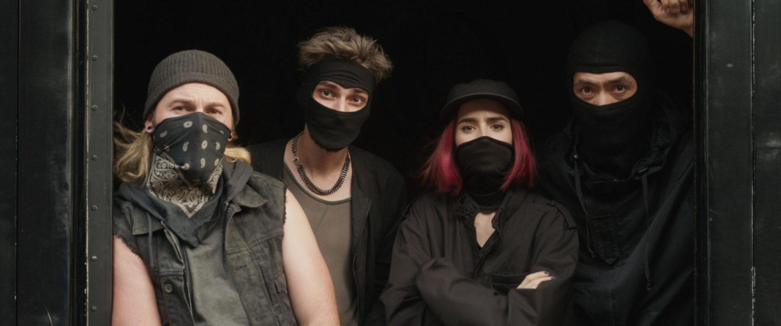 Trzech chłopaków i dziewczyna, ubrani na czarno, z kominiarkami na głowach