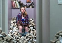 zdjęcie przedstawia dziewczynę siedzącą na toalecie, a obok niej jest sterta rolek po papierze