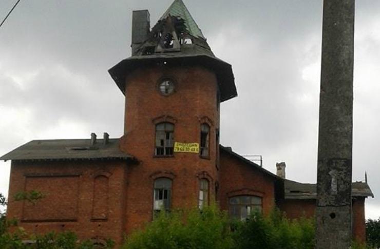 Zdjęcie opuszczonego budynku, ktory kiedys byl szkola/hotelem. Widać piętrzącą się wieże oraz rozpadający dach. Budynek jest z czerwonej cegły i mocno zaniedbany.