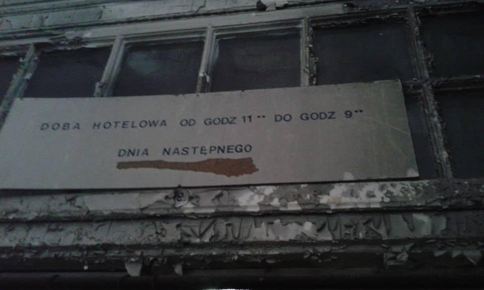 zdjęcie z wewnatrz opuszczonego budynku szkoly. Przedstawia tabliczke, ktora informuje o czasie trwania doby hotelowej.