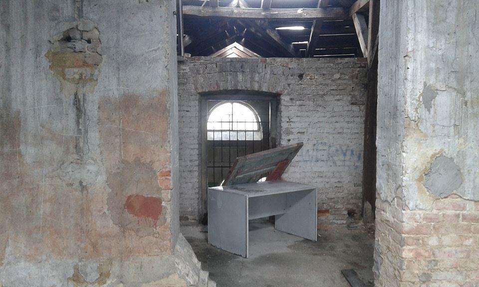 Zdjecie z wewnatrz opuszczonego budynku. Przedstawia poddasze oraz wejscie do pokoju, ktore mialo byc zagrodzone drzwiami i szafka. Sciany sa z szarej cegly