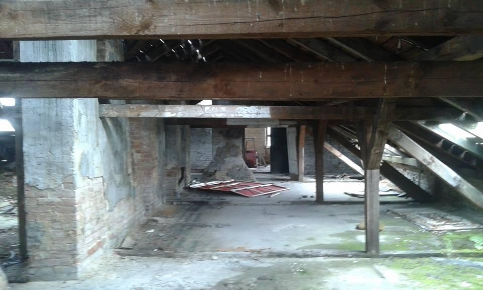 Poddasze w opuszczonej szkole. Widac drewniana konstrukcje, rozwalone meble.