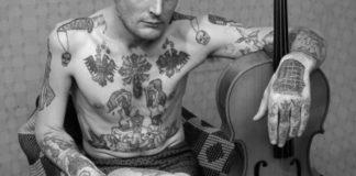 Zdjęcie rozebranego do bielizny mężczyzny, który jest cały w radzieckim tatuażach. Siedzi na fotelu, trzyma nogę na nodze a lewą rękę opiera o skrzypcę.