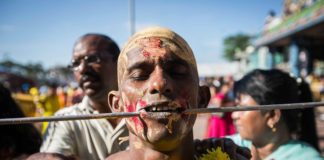 Mężczyzna z ustami przebitymi prętem i kwiecistym łancuchu na szyi