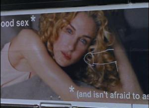 Plakat przedstawiający kobietę z kręconymi włosami i dorysowany obok penis