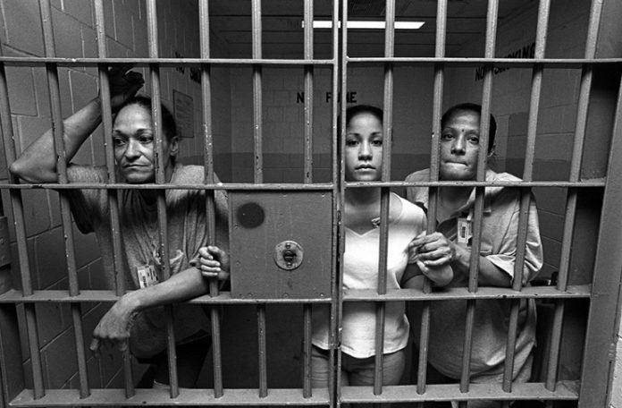 Czarno białe zdjęcie przedstawiające trzy kobiety znajdujace się za kratami więzienia. Każda z nich stoi przy kracie i lekko wystawia głowę