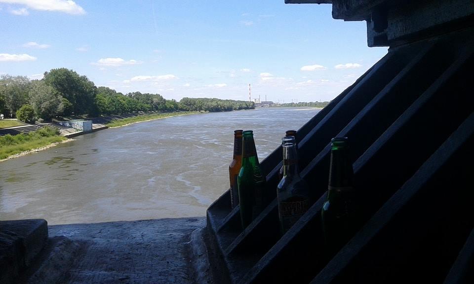 Zdjecie z nad wisły. Widac na nim filar mostu oraz pozostawione przez gości butelki po piwie. Po lewej strony rozciagacjcy sie las.
