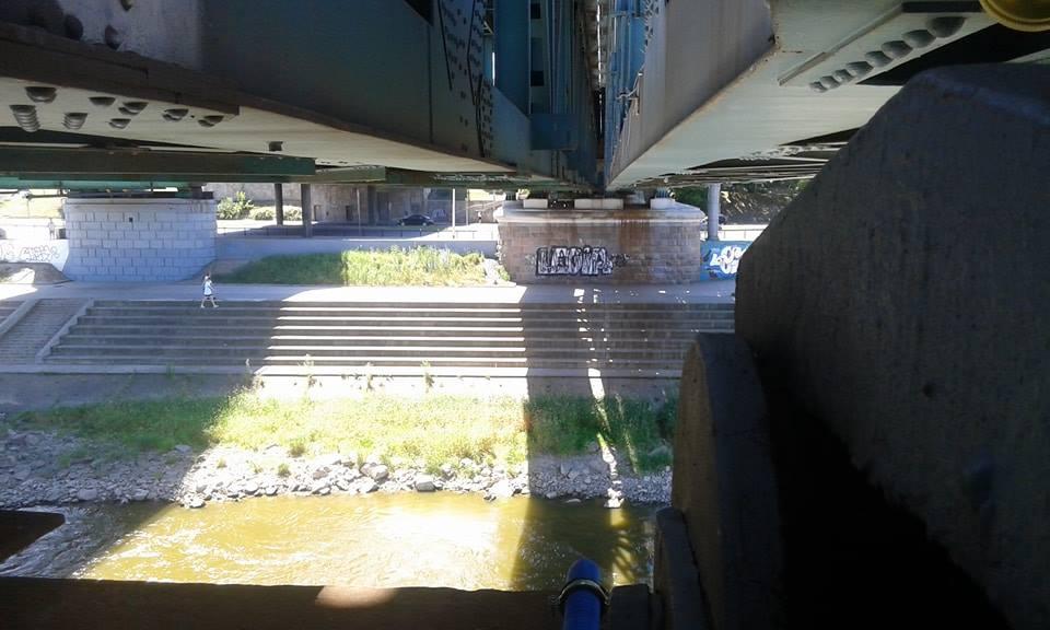 Zdjecie schodków nad wisłą widziane z filara trzymajacego most. Nie widać ludzi, samochodów, jedynie grafitii Legia na scianie