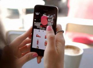 na zdjęciu są ręce dziewczyny trzymającej telefon. korzysta ona z jakiejś aplikacji modowej