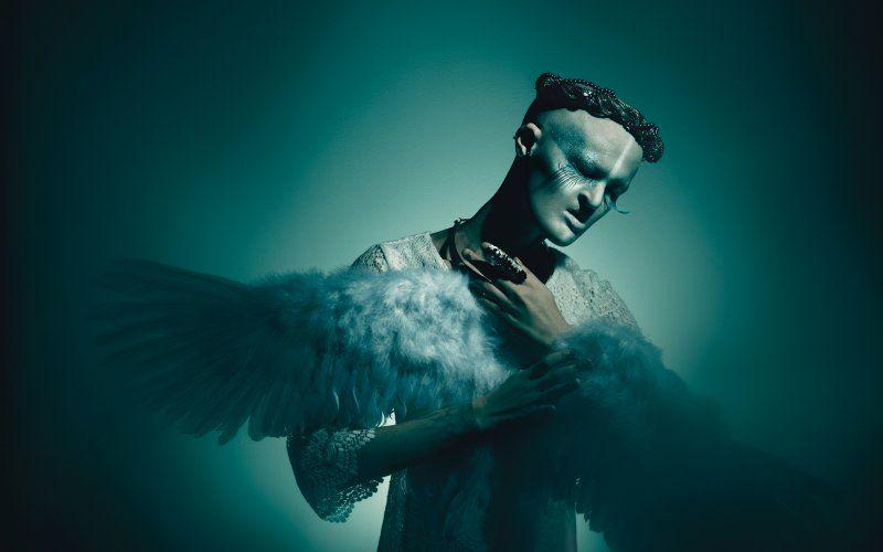Fotografia utrzymana w ciemnych kolorach, w odcieniach zieleni. Na zdjęciu widać łysą modelkę ze zdeformowaną twarzą, w wianku z czarnych koralików, trzymającą w rękach i przytulającą skrzydła z białych piór. Ubrana jest w białą koronkową sukienkę.