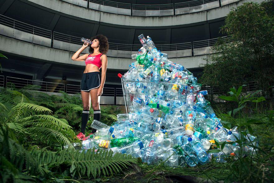 zdjęcie przedstawia dziewczynę pijącą wodę, a obok niej jest duża sterta pustych butelek po wodzie