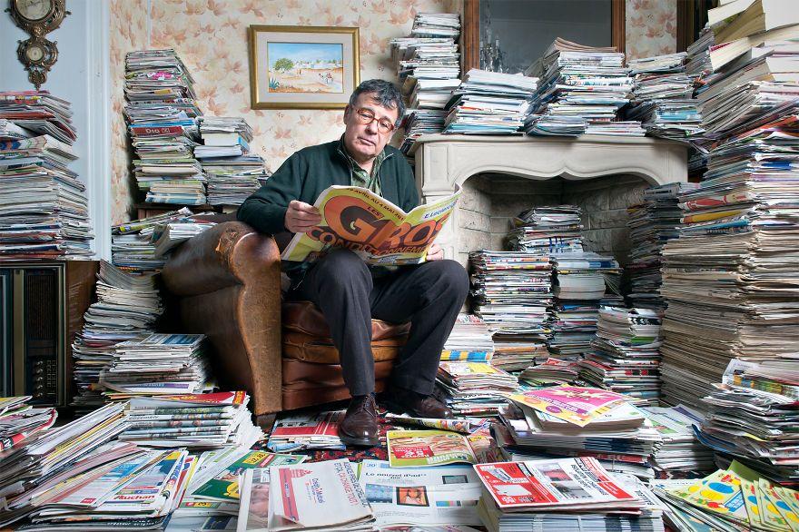 zdjęcie przedstawia mężczyznę czytającego gazetę, a obok niego jest duża sterta innych gazet