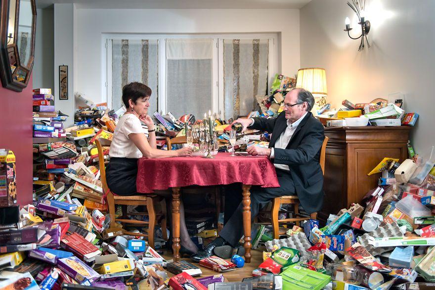 zdjęcie przedstawia małżeństwo siedzące przy stole, a wokół nich jest cały pokój zagracony pustymi opakowaniami po produktach codziennego użytku