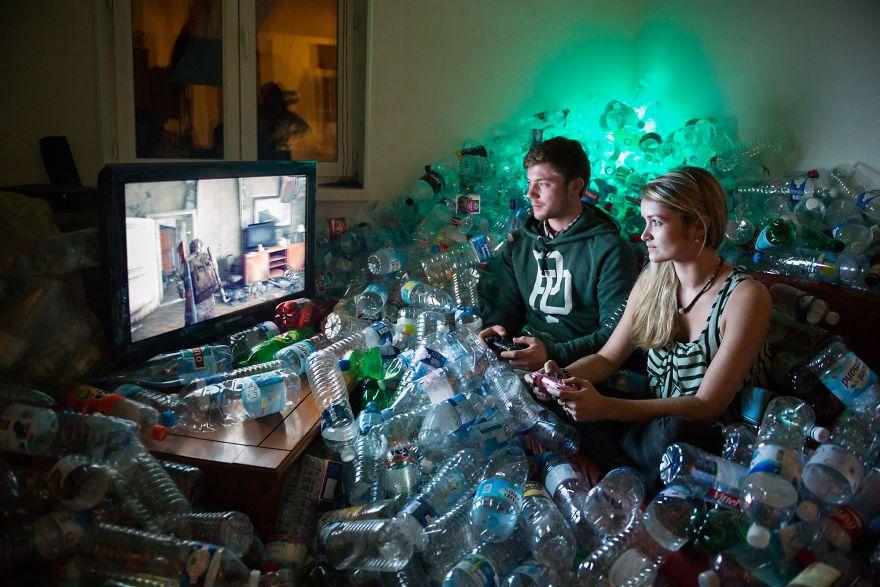 Zdjęcie przedstawia parę grającą na konsoli w otoczeniu sterty pustych butelek