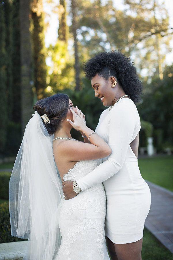 Dwie ciemnoskóre kobiety ubrane w suknie ślubne, jedna drugą obejmują w talii
