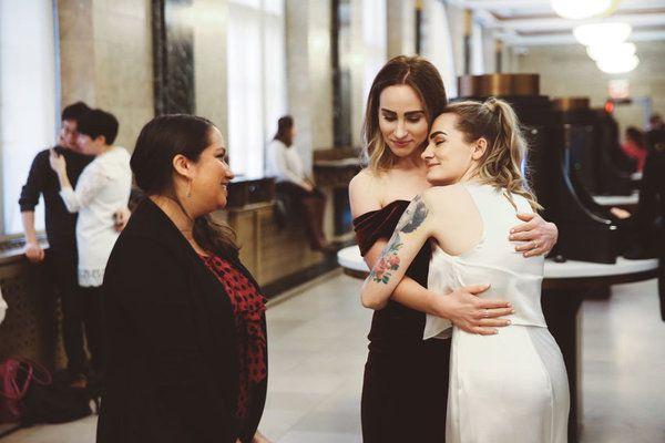 Dwie przytulające się kobiety: jedna w białej, druga w czarnej suknii i kobieta w czarnej marynarce i czerwonej bluzce stojąca obok