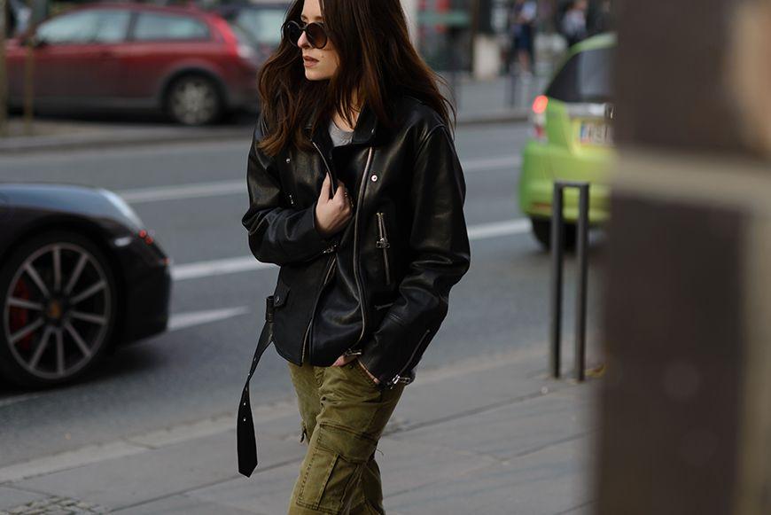 Brunetka w okularach przeciwslonecznych idzie ulica pelna samochodow ubrana w czarna ramoneske i spodnie khaki