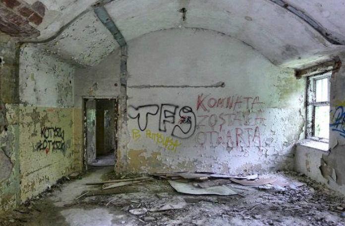 Jedno z pomieszczen w opuszczonych szpitalu w Otwocku. Widac porozbijane szklo, pomazane sciany oraz przejscie do innego pokoju