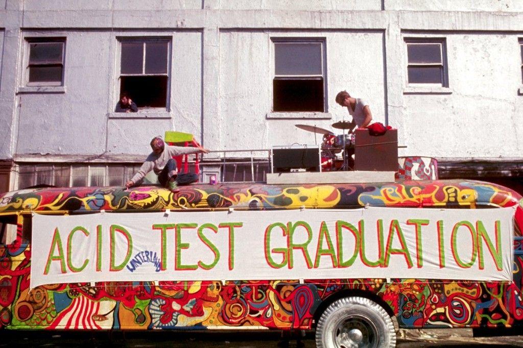 Zdjęcie autobusu pomalowanego w psychodeliczny motyw. Na jego dachu widać dwie osoby. Jedna z nich gra na perkusji, druga poprawia malunki. Autobus stoi na tle białego budynku. W jednym z jego okien widać wystająca postać.