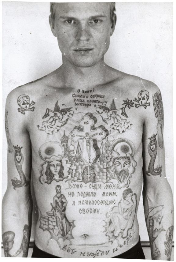 Zdjęcie męzczyzny widocznego od pasa w górę. Jego cała klatka piersiowa oraz ramiona są wytatuowane w radzieckie, więzienne wzory. Są motywy religijne, napisy cyrylicą oraz czaszki. Męzczyzna stoi na tle białej ściany.
