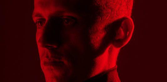 Mężczyzna ustawiony profilem w czerwonym świetle