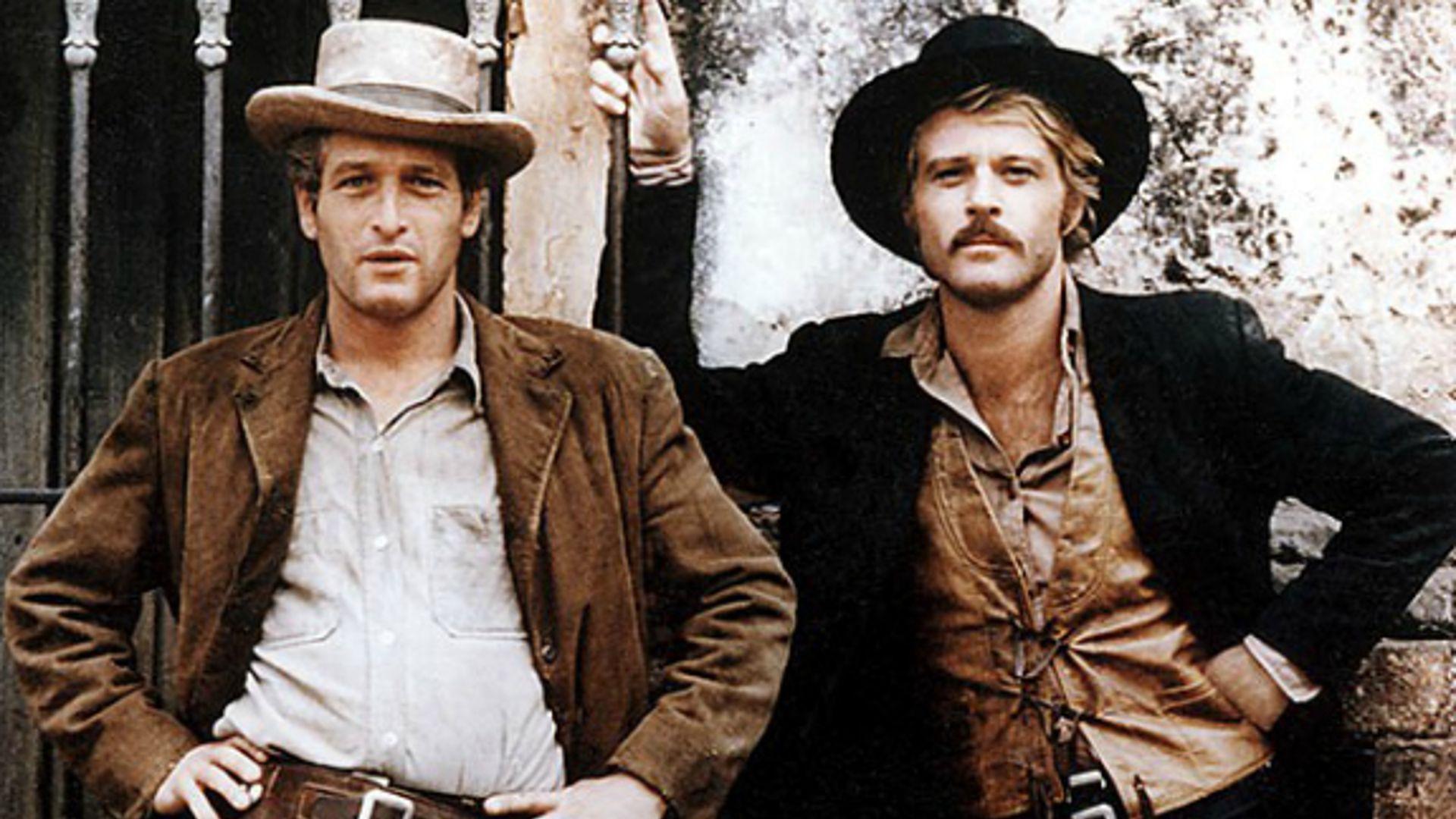 """KAdr z filmu """" Butch Cassidy and Sundance Kid"""". Widać dwóch rewolwerowców. Jeden z nich jest w brązowej marynarce i jasnej koszuli. Drugi nosi brązową koszulę i czarną marynarkę. Obydwaj stoją. Ich cechą wspólną jest kapelusz na głowie."""