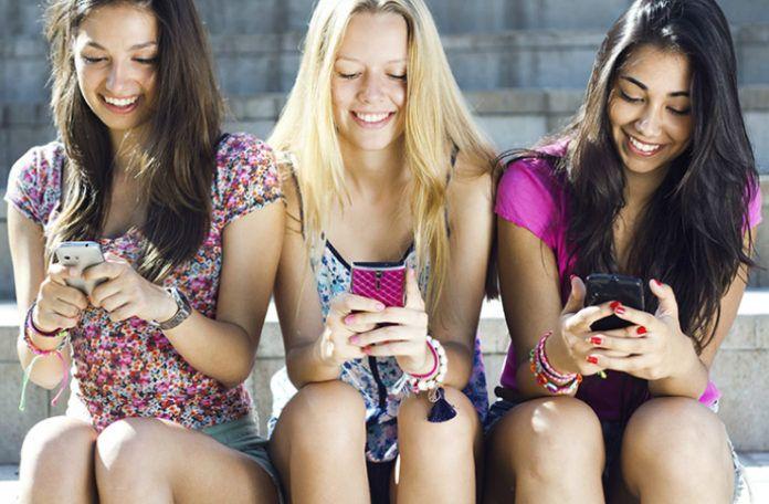 na zdjęciu są trzy dziewczyny wpatrzone w swoje telefony komórkowe