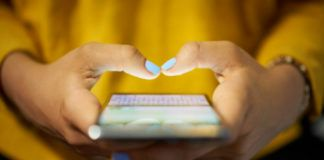 na zdjęciu widzimy dwie ręce trzymające telefon i dwa palce przymierzające się do pisania na ekranie