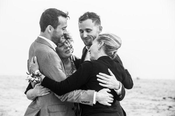 Dwie kobiety i dwóch mężczyzn stojący we wspólnym objęciu