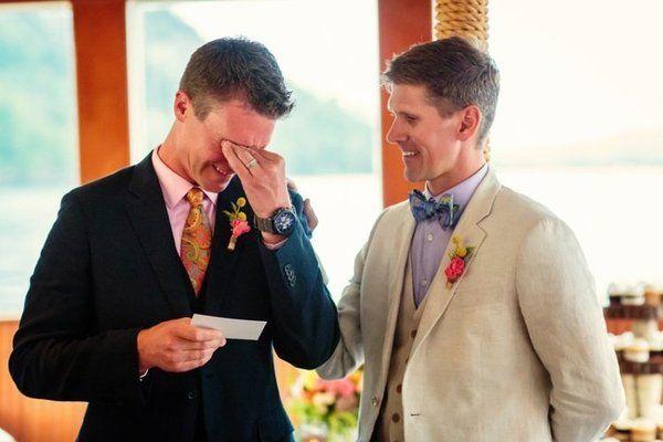 Fotografia dwóch świeżoupieczonych nowożeńców. Dwóch męzczyzn. Jeden w ciemnym garniturze stara się ukryc łzy wzruszenia, drugi natomiast w jasnym garniturze stoi obok niego dodajac mu otuchy. Urocze.