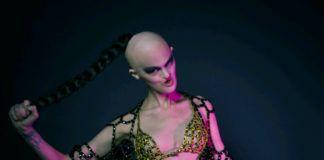 Fotografia kolorowa utrzymana w kolorach różu i fioletu. Modelka stoi w złotym bikini z łańcuchów, a na ramiona ma zarzucone czarne łańcuchy. Modelka ma zdeformowaną twarz i łysą głowę, tylko z czubka głowy wychodzi czarny warkocz, który trzyma lewą ręką.